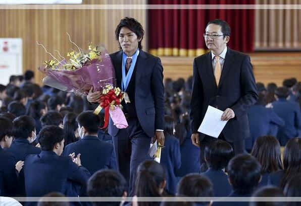 母校を訪れた際に生徒からの拍手で見送られている楢崎智亜さん