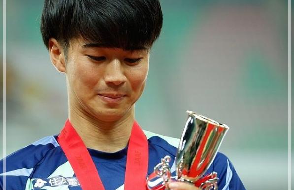 優勝カップを持ち微笑む多田修平さん。